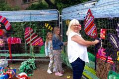 School children and passers-by weave blooming marvellous work of art