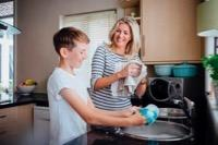 Boy washing dishes with carer - compressed