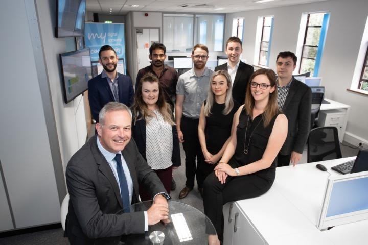 MD John Whelan (front left) with Customer Services Mgr Katie Allen (sitting right) and the My Digital Accounts team in Wilmslow